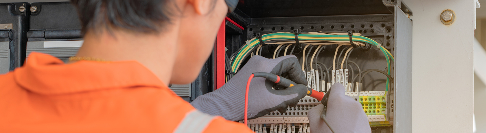 Electrical technician examining a cable junction box using zip tie cable management