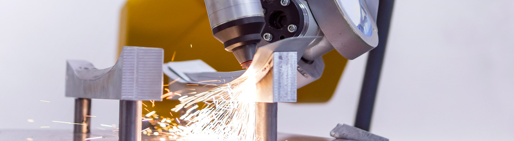 Robotic arm laser cutting metal with sparks
